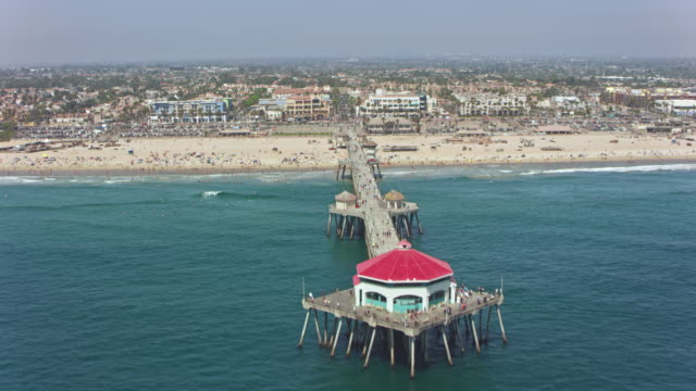 aerial from the sea towards the pier on the sandy beach of the huntington beach city, ca - north america stock videos & royalty-free footage