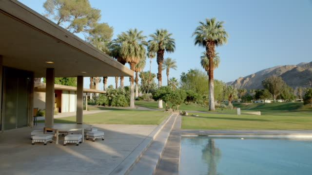 ws pan from thunderbird country club golf course to mid-century modern celebrity home featuring large roof overhang projection providing shade for living room - clubhouse stock videos & royalty-free footage
