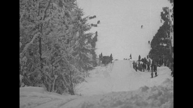 vídeos de stock e filmes b-roll de from top of jump as competitors ski down and jump one by one / vs from higher up jump / skier waxes his skis / note: exact year not known;... - depilação