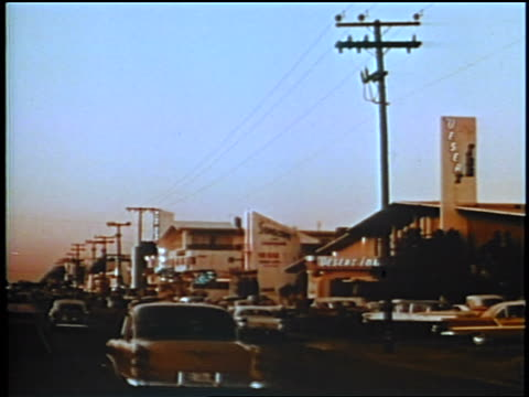 1958 pan from traffic on motel lined street to motel + parking lot / may be florida / newsreel - motel stock videos and b-roll footage