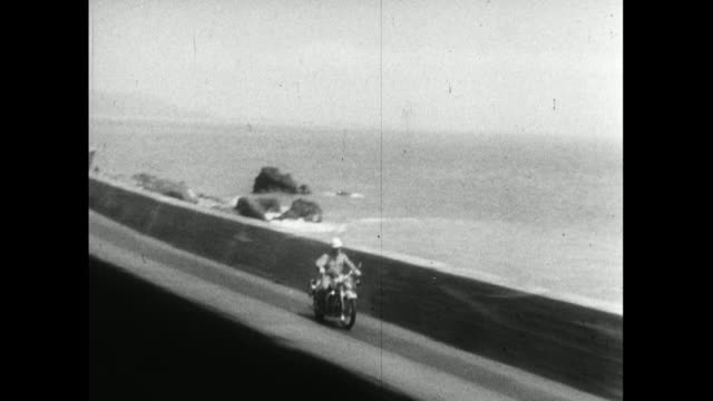 vídeos de stock e filmes b-roll de ts from train following motorbike along japan coast; 1959 - 1950