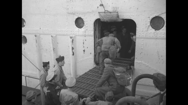from tugboat loaded with soldiers as it pulls away from ss henry ward beecher, many soldiers remaining on ship at railing / bow of tug filled with... - ホームカミング点の映像素材/bロール