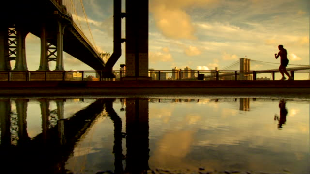vídeos de stock e filmes b-roll de large puddle of highly reflective water on ground, almost silhouette of female jogger running through frame , partial manhattan bridge & brooklyn... - ponte de manhattan