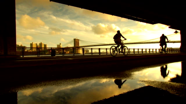 large reflective puddle of water on ground, silhouette of two unidentifiable bikers riding away from frame , partial brooklyn cityscape & brooklyn... - golden hour stock videos & royalty-free footage