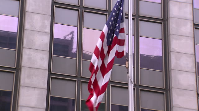 From United States flag hanging on pole to SLIGHT ANGLED WS front of Phillip Burton Federal Building CA City Hall court house