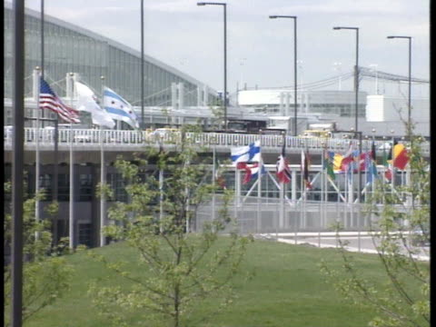 vídeos de stock, filmes e b-roll de from various country flags on poles in front of o'hare international airport to xws airport terminal building, partial driveway of frame. travel,... - chicago 'l'
