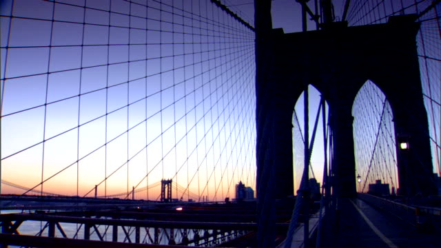 Silhouette of Brooklyn Bridge tower off center suspension cables some vehicles driving lower of frame silhouette of Manhattan Bridge Brooklyn skyline...