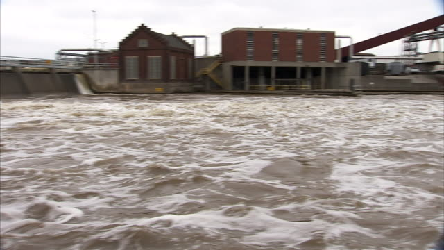 from ws water flowing from dam rushing out into grand river power plants facilities across river bg to angled ms otto e eckert station power plant... - lansing stock videos and b-roll footage