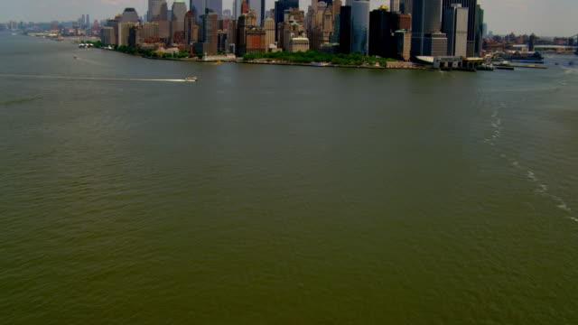 WIDE AERIAL TILT UP from water to Lower Manhattan skyline