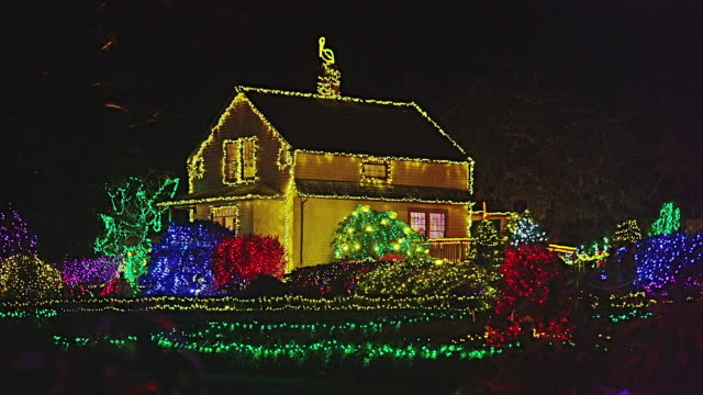 zoom out from wide shot garden house and trees and bushes decorated with christmas lights to long shot including pavilion at night in shore acres state park, coos bay, oregon - oregon us state stock videos & royalty-free footage