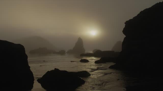 ZOOM OUT from WIDE to LONG SHOT foggy silhouetted rock formations on beach at sunset, Oregon