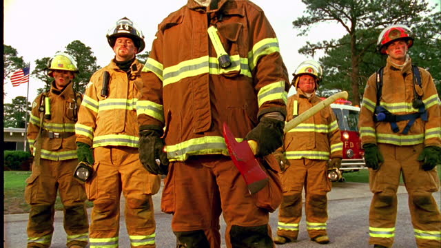 low angle dolly from wide to medium shot firefighters stand together in front of a fire station. - heroes stock videos & royalty-free footage
