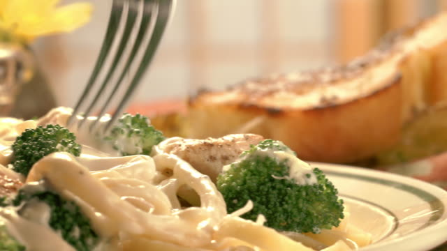cs pan  from wine bottle and toasted garlic bread to steaming plate of chicken broccoli pasta alfredo as fork lifts noodles from plate  - pasta video stock e b–roll