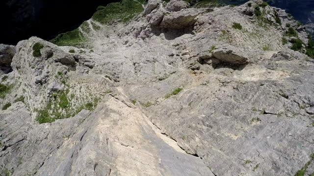 POV from wingsuit flier descending along mountain ridges