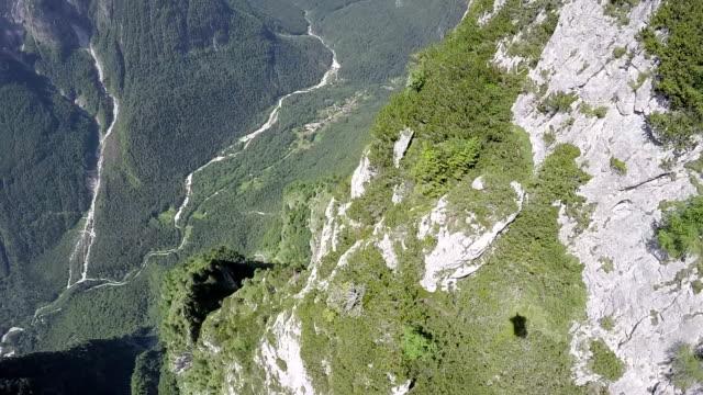 pov from wingsuit flier descending along mountain ridges - base jumper stock videos & royalty-free footage