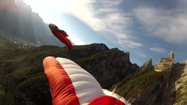 POV from wingsuit fliers wing to teammate flying