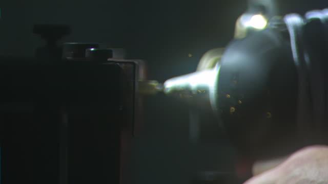 front blade of ice hockey skate sparking amp rotating against grinding stone of sharpening machine soft orange sparks flying toward camera dark bg... - 研ぐ点の映像素材/bロール