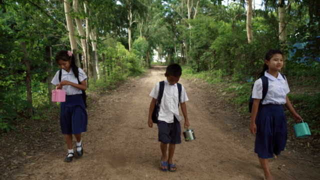 f/s steadycam front, burmese children coming back from school in a rural area - schuhwerk stock-videos und b-roll-filmmaterial