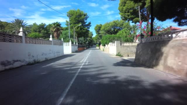 vídeos de stock e filmes b-roll de front car drive pov through treelined streets with stone houses and clear blue sky in dénia, valencian community - cidade pequena