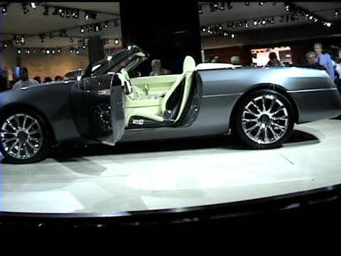 WS front end and driver side profile of Lincoln Mark X concept car revolving on turntable / WS boat tail rear end of car / CU front end passing...
