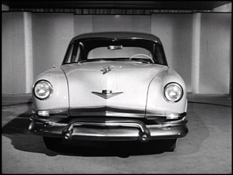 front end of 1952 kaiser manhattan revolving on turntable in studio / passenger side of car; passenger door swings open to reveal interior / rear end... - in front of点の映像素材/bロール