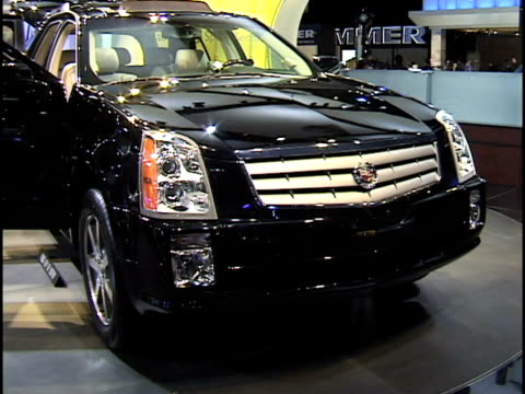 vídeos de stock e filmes b-roll de ws front end of cadillac srx revolving on turntable / ws promotional video screen showing srx marketing video 2004 cadillac srx montage at cobo hall... - cadillac