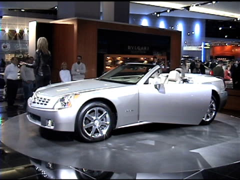 front end of cadillac xlr convertible revolving on turntable; narrator speaks nearby / white interior 2004 cadillac xlr roadster montage at cobo hall... - narrating stock videos & royalty-free footage