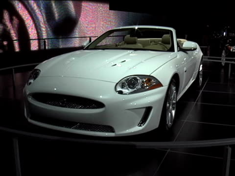ws front end of jaguar xkr convertible revolving on turntable / cu info sign 2010 jaguar xkr convertible montage at cobo hall on january 23 2009 in... - curious cumulus productions stock videos and b-roll footage