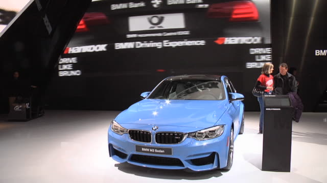 ws front end of m3 in front of giant video wall / zows passenger side profile - limousine familienfahrzeug stock-videos und b-roll-filmmaterial