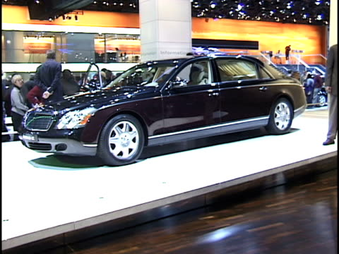 ws front end of maybach luxury sedan / ws driver side profile / ws sales rep next to car talking to spectator pan to front of car / ws v12 engine... - limousine luxuswagen stock-videos und b-roll-filmmaterial