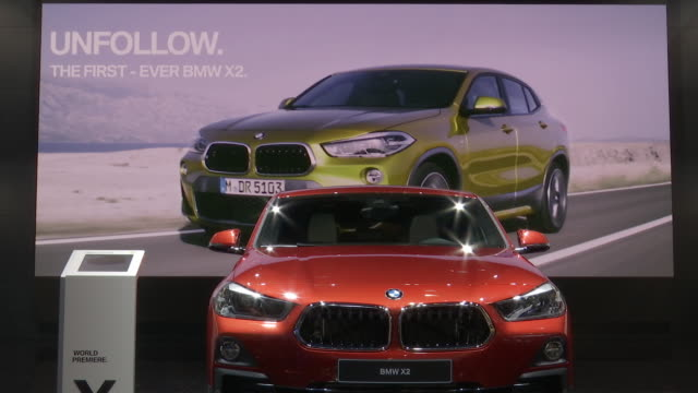 WS front end of Sunset Orange BMW X2 video wall shows promotional movie behind car / WS front quarter driver side POV of Misano Blue X2 / WS driver...