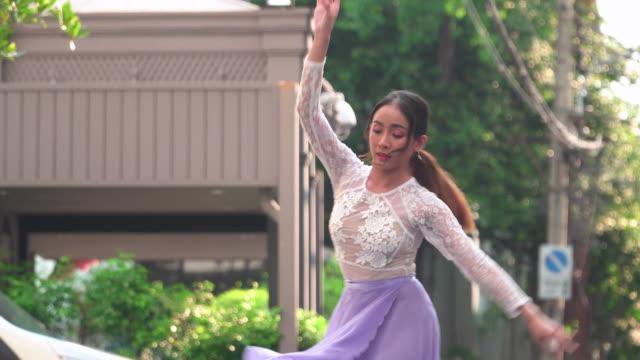 vorne: eine asiatische balletttänzerin, die im ballett auf einer lokalen straße mit stadtbild dahinter, bangkok, thailand, übt. konzept der aktiven jungen frau am wochenende aktivitäten. - akrobatische aktivität stock-videos und b-roll-filmmaterial
