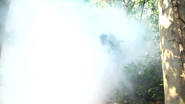 front following view: face of group of fully equipped and armed soldier appear form mist while  patrolling in tropical forest - military aeroplane stock videos & royalty-free footage
