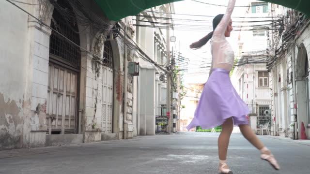 vordere ansicht: lächeln und glück einer asiatischen balletttänzerin, die im ballett auf einer lokalen straße mit altmodischem gebäude, römischem stil, bangkok, thailand, übt. konzept der aktiven jungen frau am wochenende aktivitäten. - akrobatische aktivität stock-videos und b-roll-filmmaterial