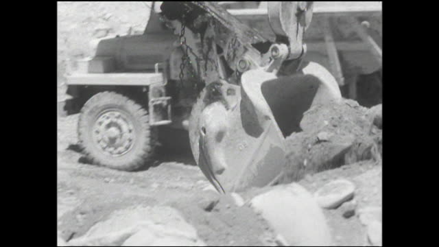 a front loader carries a load of dirt and dumps it into a truck during construction on the yagisawa dam. - 戦後点の映像素材/bロール