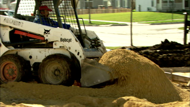 stockvideo's en b-roll-footage met a front loader operator picks up a scoop of soil and dumps it into a truck. available in hd. - aangelegd