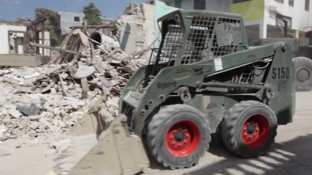a front loader removes earthquake debris as an armed soldier walks nearby. - 2010 video stock e b–roll