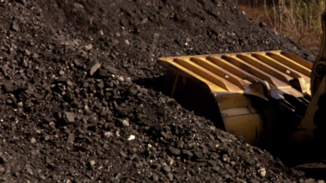 a front loader scoops coal from a pile. - kohle stock-videos und b-roll-filmmaterial