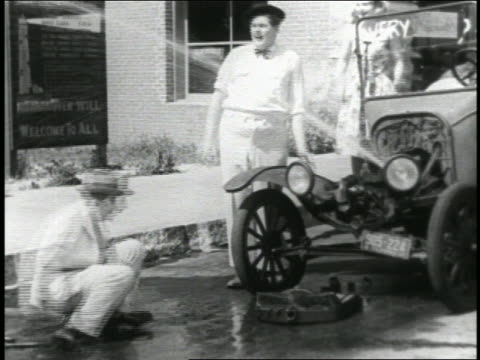 b/w 1920 front of car falling off + water shoots out by 2 men / fat man's pants fall down / feature - anno 1920 video stock e b–roll