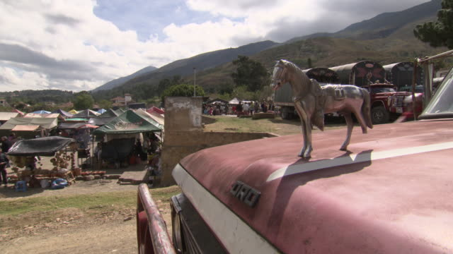 front of ford pickup truck with chrome horse figurehead in foreground with colorful trucks and busy market in background, villa de leyva market, villa de leyva, boyacã¡ department, colombia - ford truck stock videos and b-roll footage