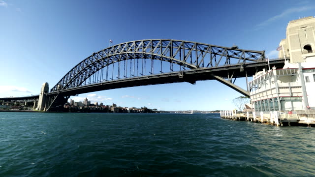 ws sydney harbour approaching harbour bridge city buildings on shoreline left pier one sydney harbour waterfront hotel right opera house appearing bg - bennelong point stock videos and b-roll footage
