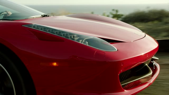 vídeos y material grabado en eventos de stock de front of red ferrari driving down malibu canyon with pacific ocean in background - ferrari