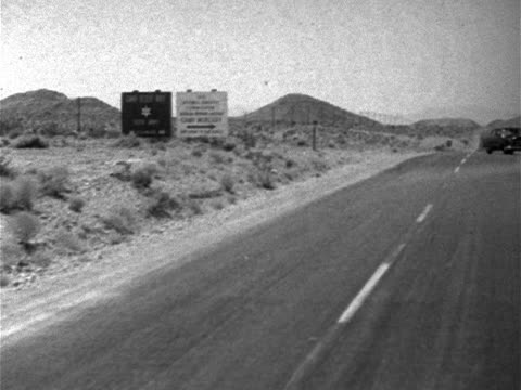vidéos et rushes de sign 'us atomic energy commission nevada proving ground camp mercury' turning off main road nts nevada test site restricted testing radioactive cold... - 1952