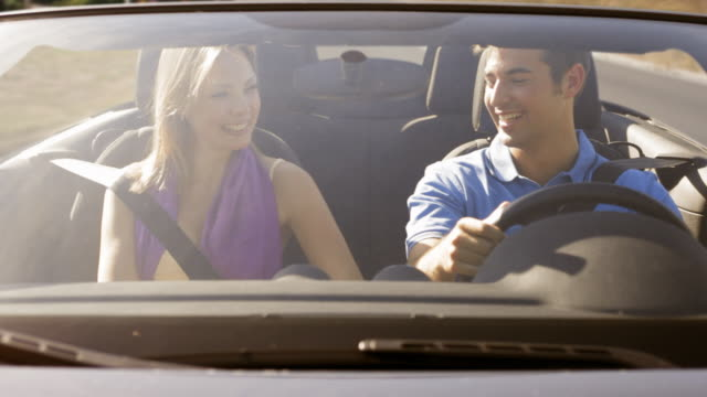 front on shot of young couple in convertible car - land vehicle stock videos & royalty-free footage