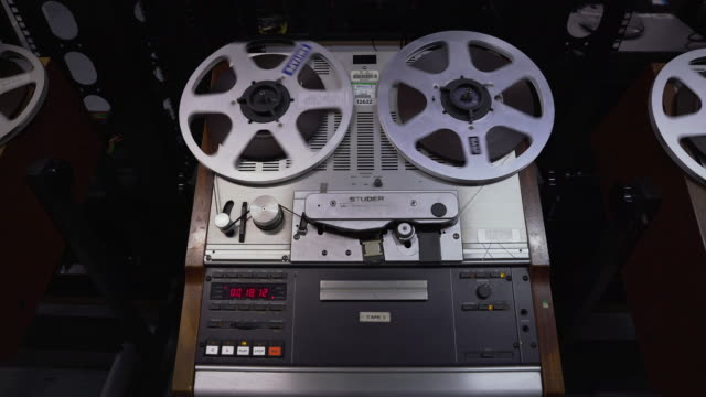 Front on static shot of a shot of a 'Struder' reel to reel film player during playback