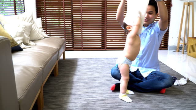 front panning view: 2 year old son getting dressed from his young father - genderblend stock videos & royalty-free footage