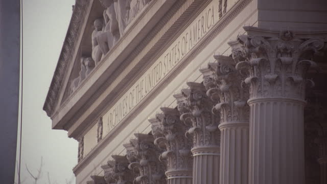 stockvideo's en b-roll-footage met selective focus front pediment of national archives building with columns, entablature, ionic columns and capitals, and engraving denoting archives of the united states of america / washington, d.c., united states - national archives washington dc
