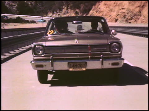vidéos et rushes de ws tracking shot front quarter driver side view of 1966 rambler american 440 on california highway / ws tracking shot rear three quarter view of... - bord de route