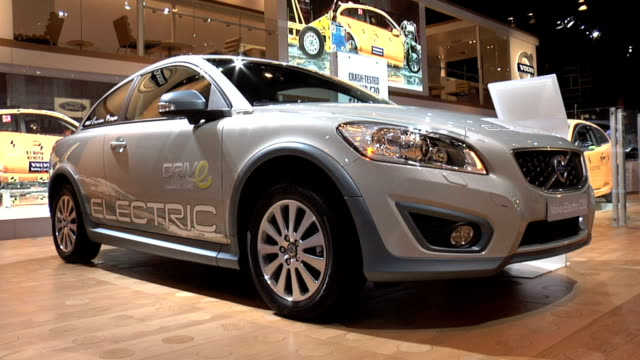 "front quarter passenger side of volvo c30; front end of car; tilt down to ""electric"" type on edge of hood / info sign on wall / front end of... - crash test stock videos & royalty-free footage"
