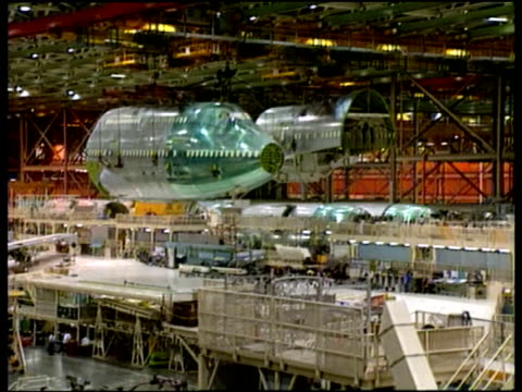Front section of airplane body moved by overhead pulleys at Boeing plant